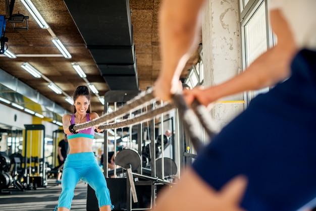 Привлекательная счастливая игривая активная фитнес-девушка тянет веревки со своим тренером в солнечном современном тренажерном зале.