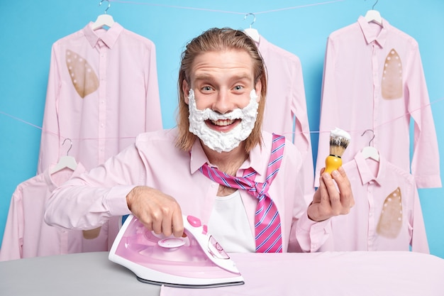 Il marito attraente e felice dai capelli rossi si rade e accarezza i vestiti per il lavoro a casa sembra positivamente usa le pose del ferro elettrico sul blu