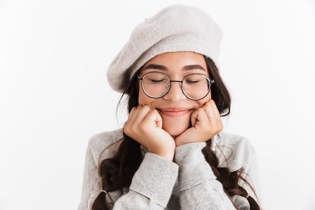 白い壁の上に孤立して立っているunifromを身に着けている魅力的な幸せな女子高生、目を閉じて