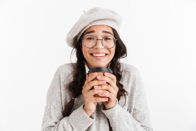 흰색 벽에 고립 된 unifrom을 입고 테이크 아웃 커피 컵을 들고 매력적인 행복 여학생