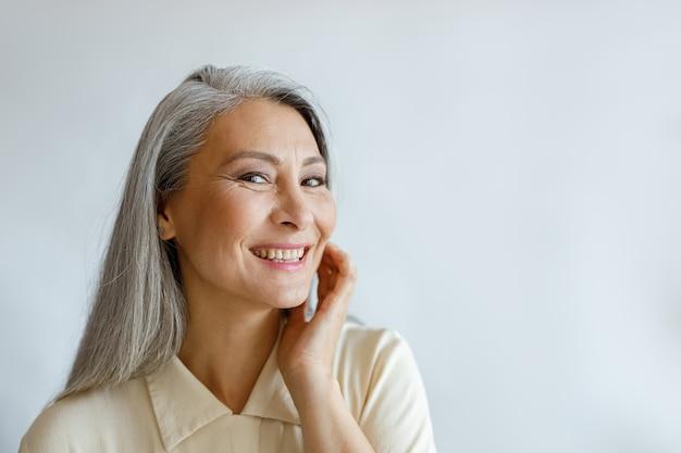 Привлекательная счастливая седая женщина в бежевой рубашке трогает щеку, улыбаясь на светло-сером фоне в студии. образ жизни зрелой красоты