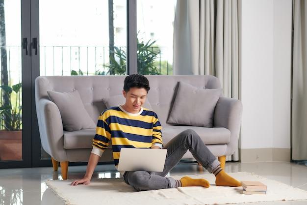 거실 바닥에 앉아 노트북 컴퓨터 작업을 하는 매력적인 행복한 똑똑한 청년