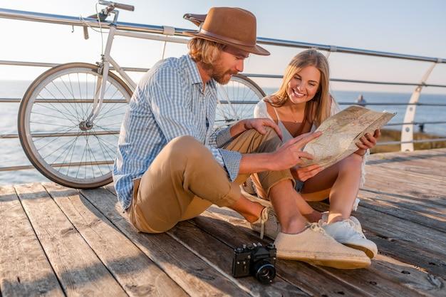 Attraente coppia sorridente felice che viaggiano in estate dal mare in bicicletta