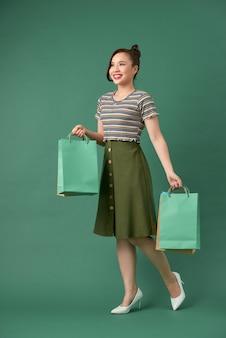 カラフルな買い物袋を保持している魅力的な幸せな笑顔のスタイリッシュな女性