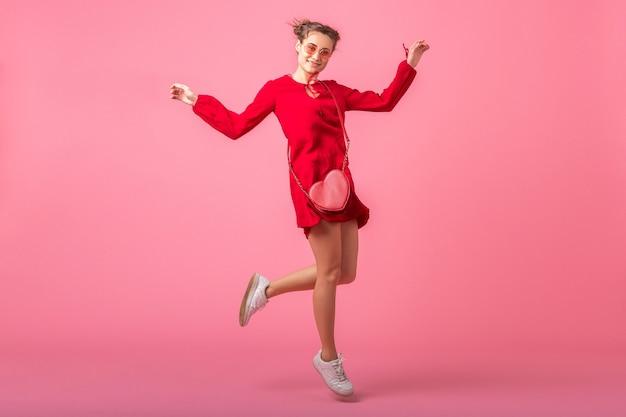 Привлекательная счастливая улыбающаяся стильная женщина в красном модном платье, прыгающая, танцующая на розовой стене, изолирована, весенне-летняя мода, романтическое настроение кокетливой девушки