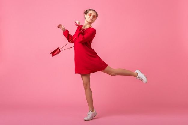 孤立したピンクの壁、春夏のファッショントレンド、ロマンチックな気分の軽薄な女の子の上を走って赤いトレンディなドレスジャンプで魅力的な幸せな笑顔のスタイリッシュな女性