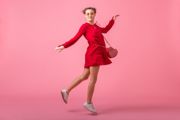 Привлекательная счастливая улыбающаяся стильная женщина в красном модном платье, прыгающая на розовой стене, изолирована, весенне-летняя мода, романтическое настроение кокетливой девушки