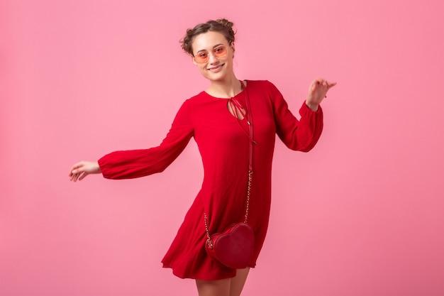 분홍색 벽 절연, 봄 여름 패션 트렌드, 세인트 발레 나이트의 날, 낭만적 인 분위기의 유혹 소녀에서 실행 점프 빨간색 유행 드레스에 매력적인 행복 미소 세련된 여자