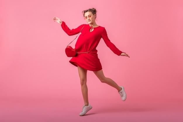 分離されたピンクの壁、春夏のファッショントレンド、聖バレナイトの日、ロマンチックな気分の軽薄な女の子の上を走って赤いトレンディなドレスジャンプで魅力的な幸せな笑顔のスタイリッシュな女性