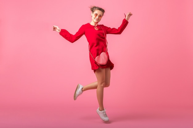 Attractive happy smiling stylish woman in red trendy dress jumping dancing on pink wall isolated, spring summer fashion trend, romantic mood flirty girl