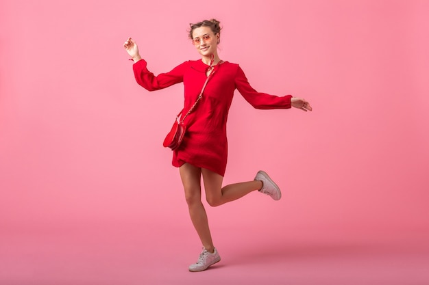 Attractive happy smiling stylish woman in red trendy dress jumping running on pink wall isolated, spring summer fashion trend, romantic mood flirty girl