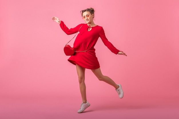 Attractive happy smiling stylish woman in red trendy dress jumping running on pink wall isolated, spring summer fashion trend, saint valenite's day, romantic mood flirty girl