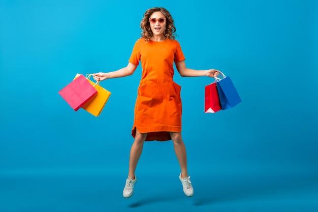 오렌지 유행 특대 드레스에 매력적인 행복 미소 세련 된 여자 쇼핑 고립 파란색 배경에 쇼핑 가방을 들고 실행 점프