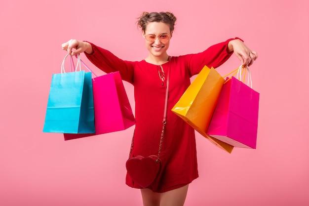 Привлекательная счастливая улыбающаяся стильная женщина-шопоголик в красном модном платье, держащая красочные сумки на розовой стене, изолированные, возбужденные продажи, модная тенденция