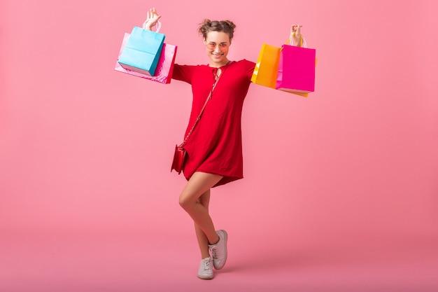 Привлекательная счастливая улыбающаяся стильная женщина-шопоголик в красном модном платье, держащая красочные сумки на розовой стене, изолированные, возбужденные продажи, весенне-летняя модная тенденция