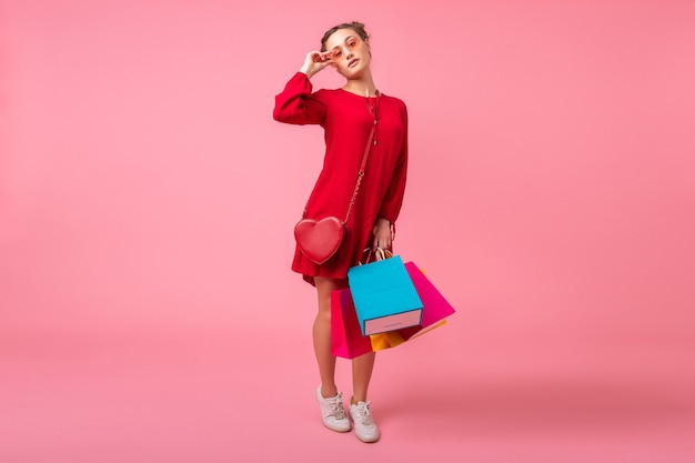 ピンクの壁にカラフルなショッピングバッグを保持している赤いトレンディなドレスで買い物中毒の魅力的な幸せな笑顔のスタイリッシュな女性は、分離、販売興奮、春夏のファッショントレンド