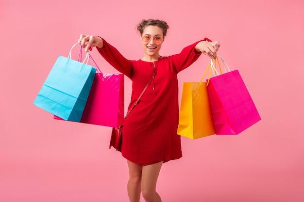 Привлекательная счастливая улыбающаяся стильная женщина-шопоголик в красном модном платье прыгает, бегая, держа красочные сумки на розовой стене, изолирована, распродажа взволнована, тенденция моды весна-лето