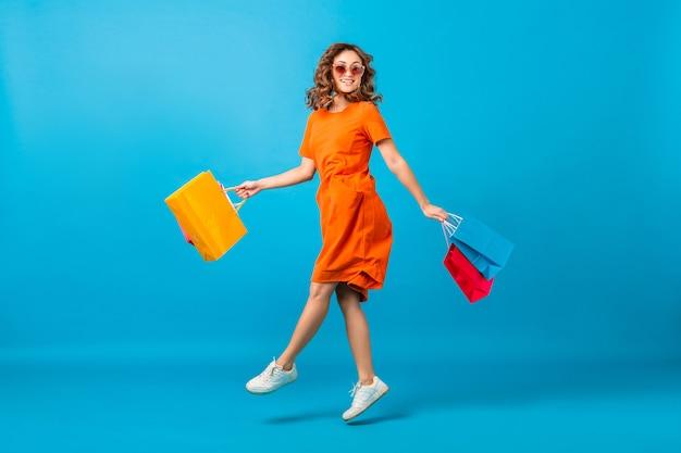 Donna alla moda sorridente felice attraente shopaholic in vestito oversize alla moda arancione che salta i sacchetti della spesa della tenuta su fondo blu dello studio isolato
