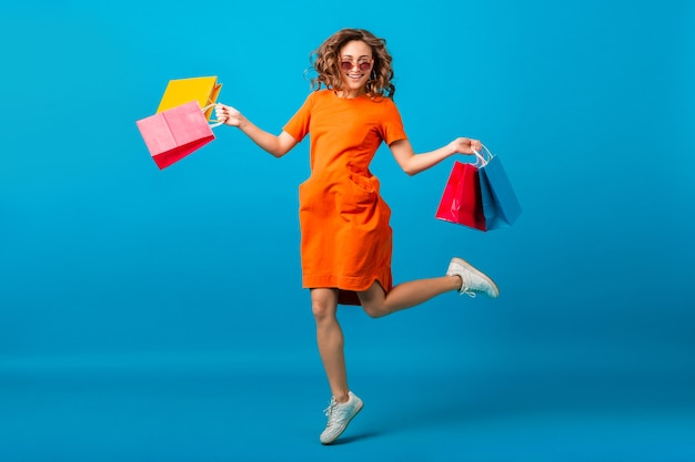 Attractive happy smiling stylish woman shopaholic in orange trendy oversize dress jumping holding shopping bags on blue studio background isolated