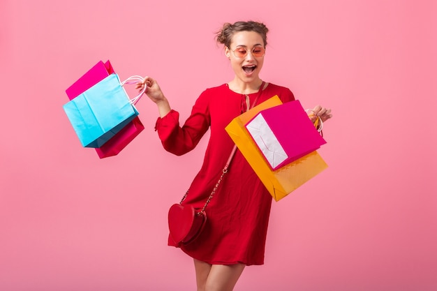 Attractive happy smiling stylish woman shopaholic in red trendy dress holding colorful shopping bags on pink wall isolated, sale excited, fashion trend