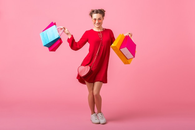 Attractive happy smiling stylish woman shopaholic in red trendy dress holding colorful shopping bags on pink wall isolated, sale excited, spring summer fashion trend