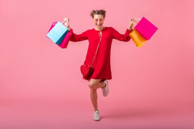 Donna alla moda sorridente felice attraente shopaholic in vestito alla moda rosso che tiene le borse della spesa colorate sul muro rosa isolato, vendita eccitata, tendenza moda primavera estate