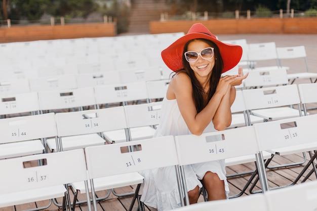 Привлекательная счастливая улыбающаяся женщина, одетая в белое платье, красную шляпу, солнцезащитные очки, сидя в одиночестве в летнем театре под открытым небом, много стульев, весенний уличный модный тренд, машет рукой привет