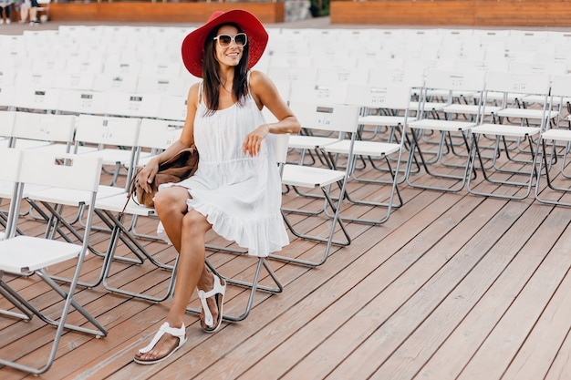 白いドレス、赤い帽子、一人で夏の野外劇場に座っているサングラス、多くの椅子、春のストリートスタイルのファッショントレンドに身を包んだ魅力的な幸せな笑顔の女性、手を振ってこんにちは