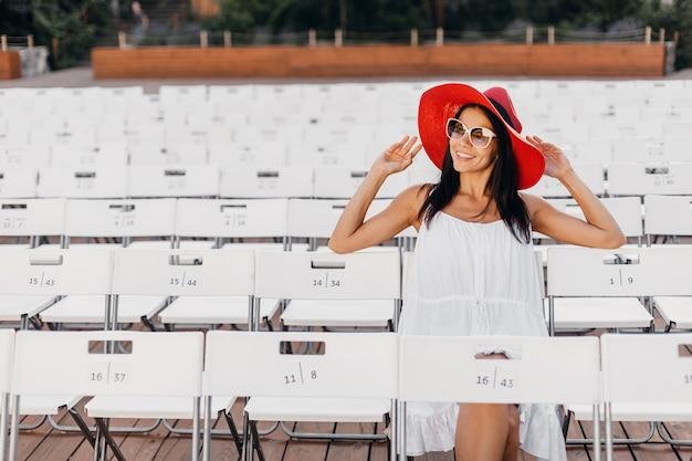 Привлекательная счастливая улыбающаяся женщина, одетая в белое платье, красную шляпу, солнцезащитные очки, сидя в летнем театре под открытым небом на стуле, весенняя уличная мода