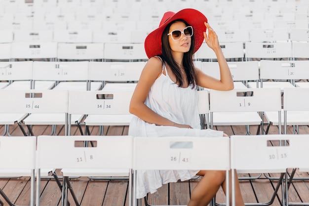 白いドレス、赤い帽子、椅子だけで夏の野外劇場に座っているサングラス、春のストリートスタイルのファッショントレンドに身を包んだ魅力的な幸せな笑顔の女性