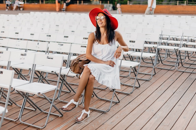 Attractive happy smiling woman dressed in white dress, red hat, sunglasses sitting in summer open air theatre alone, many chairs, spring street style fashion trend, waving hand hello