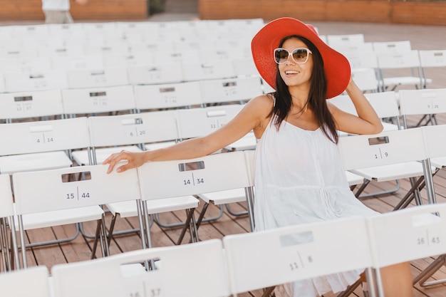 Attraente donna sorridente felice vestita in abito bianco, cappello rosso, occhiali da sole seduti in un teatro all'aperto estivo sulla sedia da solo, tendenza della moda primavera street style