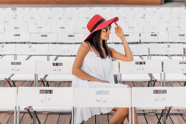 Attractive happy smiling woman dressed in white dress, red hat, sunglasses sitting in summer open air theatre on chair alone, spring street style fashion trend
