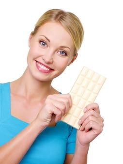 Привлекательная счастливая улыбающаяся женщина, держащая сладкую белую плитку шоколада - изолированную на белом. копировать пространство