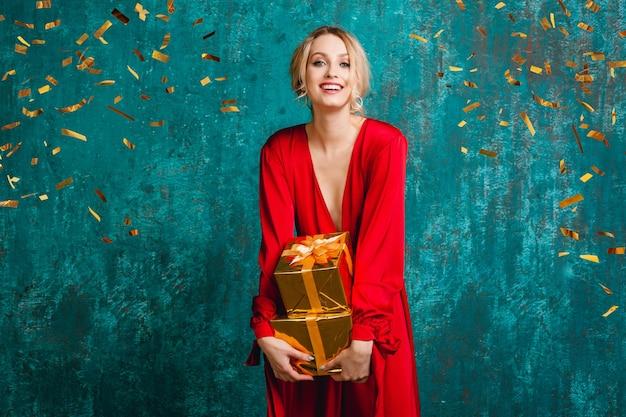 Привлекательная счастливая улыбающаяся женщина в стильном красном платье празднует рождество и новый год с подарками