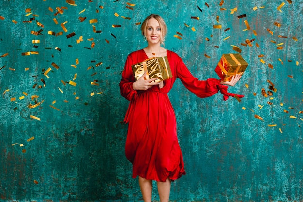 크리스마스와 새 해 선물을 축하하는 세련된 빨간 드레스에 매력적인 행복 웃는 여자