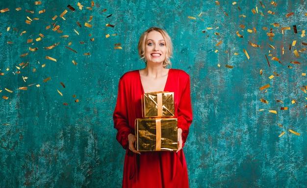 Donna sorridente felice attraente in vestito rosso alla moda che celebra il natale e il nuovo anno con i regali