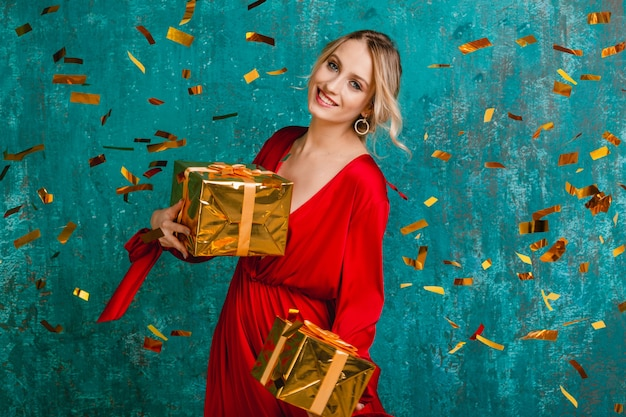 Attractive happy smiling woman in stylish red dress celebrating christmas and new year with gifts
