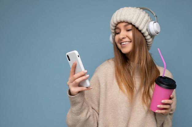 ベージュのセーターとベージュの帽子の白いヘッドフォンを身に着けている魅力的な幸せな笑顔の若いブロンドの女性
