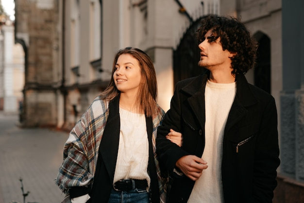 Attractive happy smiling young man and girl stylish couple in love walking hugging on the street