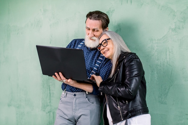 Attractive happy stylish senior couple, man and woman, leaning on green wall and embracing each other, while using laptop computer, enjoying time together