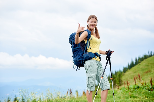 Attractive happy woman backpacker hiking mountain trail, walking on grassy hill, using trekking sticks, smiling to the camera and showing thumbs up. outdoor activity, tourism concept