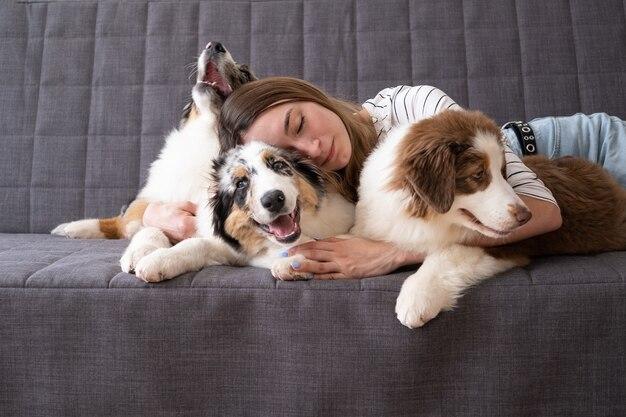 Привлекательные счастливые объятия женщины лежа на трех милых австралийских овчарках блю мерле красных трех цветах щенка. лежа на диване. любовь и дружба между человеком и животным.