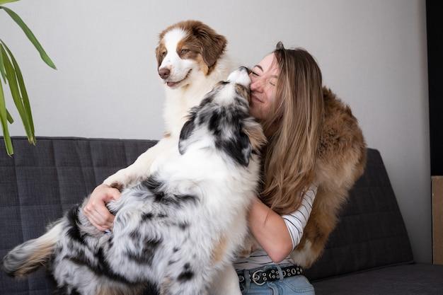 Привлекательная счастливая женщина держит поцелуй 2 маленькая милая австралийская овчарка щенок блю мерль.