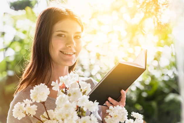Attractive happy woman holding book and bunch of flower twigs