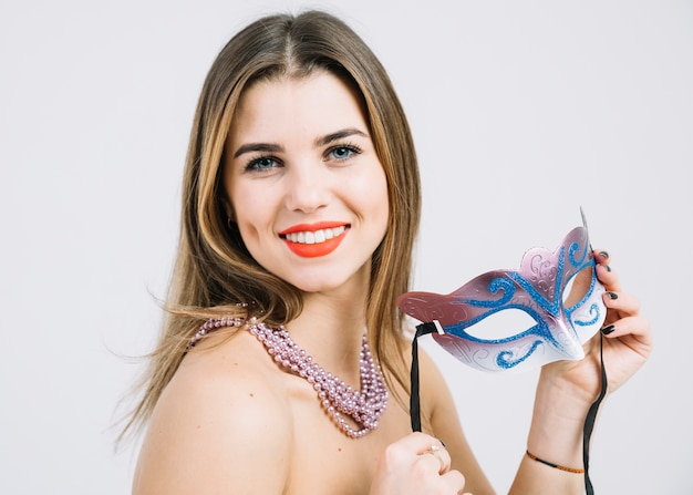 Attractive happy woman holding carnival mask on white backdrop