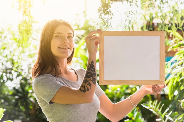 Attractive happy woman holding photo frame between plants