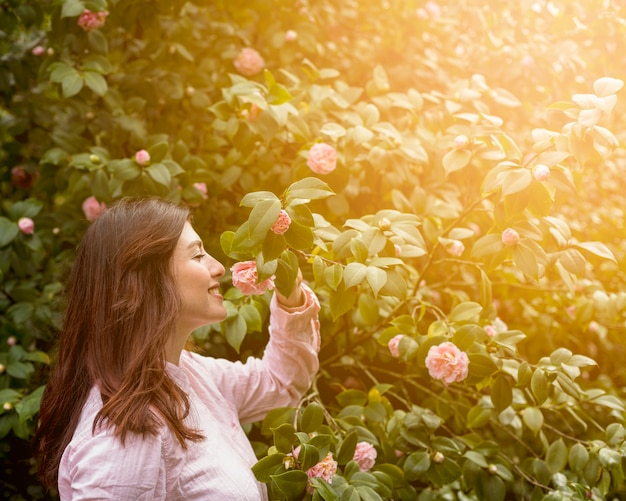 Attractive happy woman holding pink flower growing on green twig