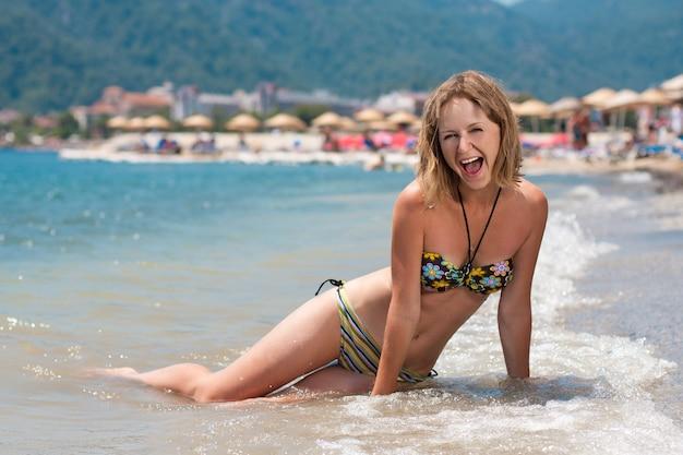 ビーチに座っているセクシーな水着で魅力的な幸せな女。マルマリスのトルコのリゾート。トルコの海岸で夏休みに濡れた髪と感情的な笑顔の女の子。