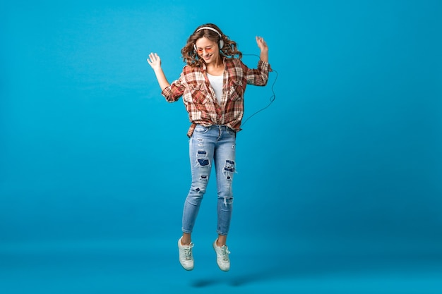 Attractive happy woman jumping in cheerful mood listening to music in headphones in checkered shirt and jeans isolated on blue studio background